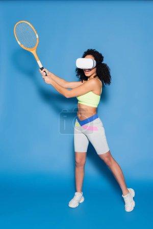 Photo pour Pleine longueur de frisée afro-américaine en vr casque jouer au tennis sur bleu - image libre de droit