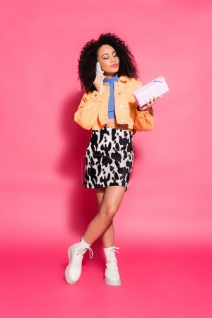full length of african american woman in skirt with animal print holding present while talking on smartphone on pink