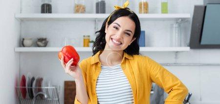 femme brune souriante tenant poivron rouge, bannière