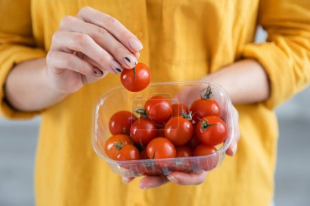 cropped view of young woman holding plastic container with ripe cherry tomatoes