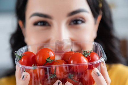 blurred young woman holding plastic container with ripe cherry tomatoes