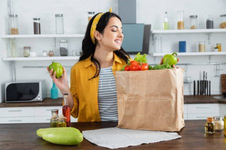 Photo for Happy brunette woman looking at paper bag with fresh groceries on kitchen table - Royalty Free Image