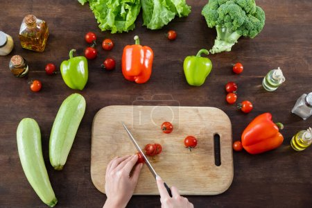top view of woman cutting cherry tomatoes on chopping board near vegetables