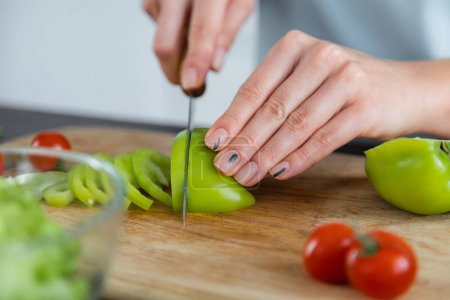 close up of woman cutting ripe bell pepper on chopping board