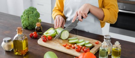 cropped view of woman in apron cutting zucchini near cherry tomatoes on chopping board, banner