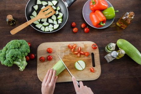 top view of woman cutting zucchini near sliced cherry tomatoes on chopping board and frying pan on table