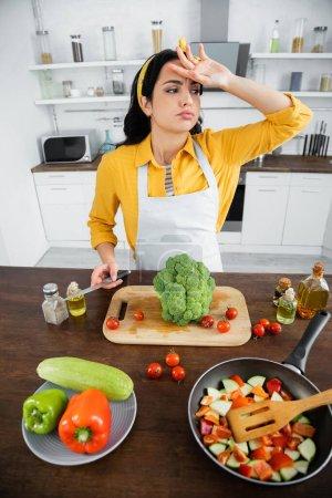 Müde junge Frau in Schürze wischt Schweiß, während sie Messer in der Nähe von Gemüse und Pfanne in der Küche hält