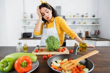 Photo pour Jeune femme fatiguée dans tablier regardant les légumes près de la poêle dans la cuisine - image libre de droit