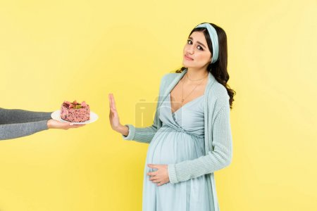 pregnant woman looking at camera while showing stop sign near cake isolated on yellow