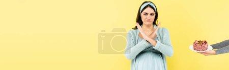 Unzufriedene Schwangere zeigt Ablehnungsgeste in Tortennähe auf gelbem Transparent