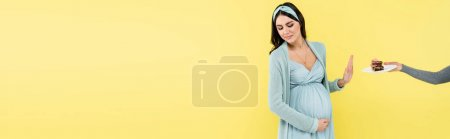 Photo for Pregnant woman showing stop gesture near piece of cake isolated on yellow, banner - Royalty Free Image