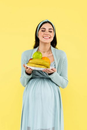 happy pregnant woman with closed eyes holding plate with fresh fruits isolated on yellow