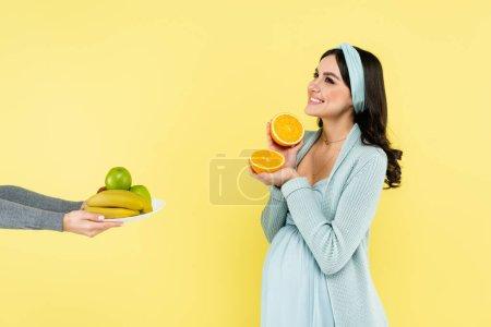 Photo pour Joyeuse femme enceinte tenant la moitié de l'orange juteuse près de fruits frais isolés sur jaune - image libre de droit