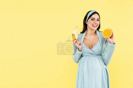 glücklich schwangere Frau lächelt in die Kamera, während sie Banane und saftige Orange isoliert auf gelb hält