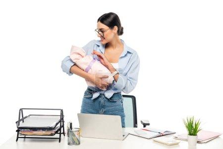 Photo pour Jeune femme d'affaires souriant à l'enfant en bas âge tout en se tenant près du bureau isolé sur blanc - image libre de droit