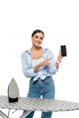 happy housewife pointing at smartphone with blank screen near ironing board isolated on white