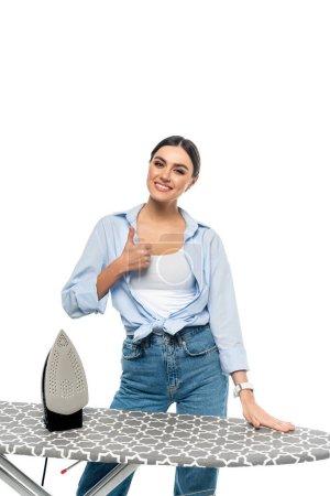 Photo pour Femme heureuse dans des vêtements à la mode montrant pouce vers le haut près de planche à repasser isolé sur blanc - image libre de droit