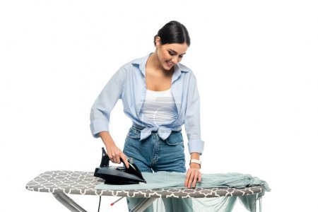 happy housewife smiling while ironing clothes isolated on white