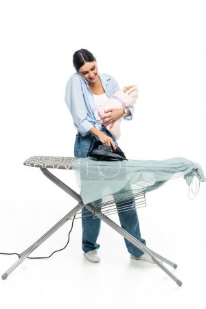 mujer alegre hablando en el teléfono móvil mientras está de pie cerca de la tabla de planchar con el niño sobre fondo blanco