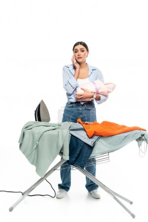 tired woman with infant baby talking on smartphone near ironing board on white background