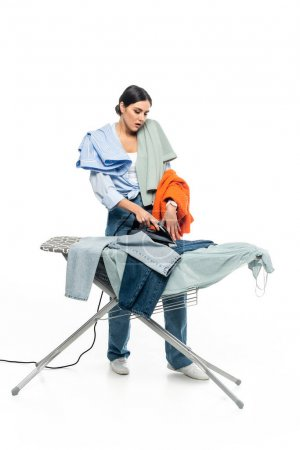 full length view of tired housewife ironing clothes on white background