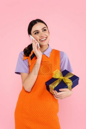 Photo for Happy woman holding gift box while talking on smartphone isolated on pink - Royalty Free Image