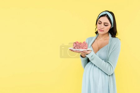 Photo pour Doute, femme enceinte tenant morceau de délicieux gâteau isolé sur jaune - image libre de droit
