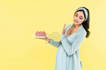 pregnant woman showing refuse gesture while holding sweet dessert isolated on yellow