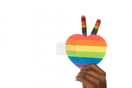 cropped view of african american man showing victory gesture and lgbt colors paper heart isolated on white