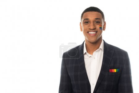 Photo pour Heureux homme d'affaires afro-américain avec drapeau lgbt peint sur le visage souriant à la caméra isolé sur blanc - image libre de droit
