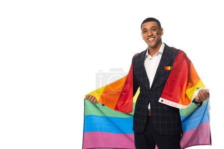 Photo pour Heureux homme d'affaires afro-américain tenant drapeau lgbt tout en souriant à la caméra isolé sur blanc - image libre de droit