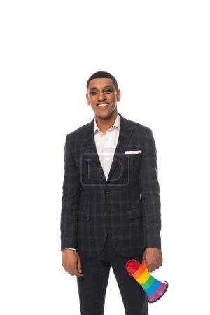 Photo pour Homme d'affaires afro-américain souriant tenant mégaphone dans des couleurs lgbt isolé sur blanc - image libre de droit