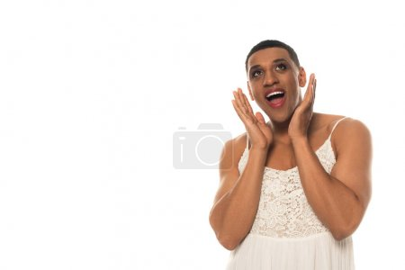 amazed african american gay man in sundress holding hands near face isolated on white