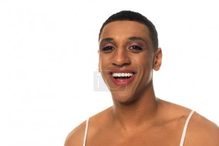 cheerful african american androgynous man with makeup smiling at camera isolated on white