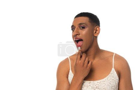 Photo pour Afro-américain transgenre homme en robe de soleil regardant caméra tout en appliquant rouge à lèvres isolé sur blanc - image libre de droit