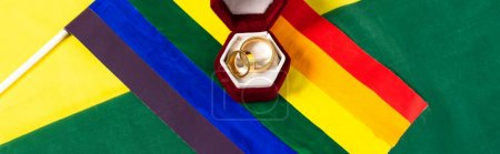 top view of lgbt flag and jewelry box with wedding rings on rainbow colors background, banner