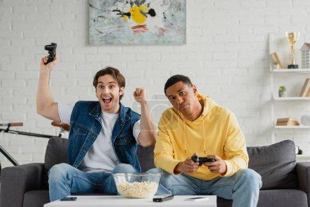 Photo pour KYIV, UKRAINE - 22 MARS 2021 : jeunes amis interraciaux jouant au jeu vidéo avec des joysticks dans le salon moderne - image libre de droit