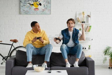 Photo pour KYIV, UKRAINE - 22 MARS 2021 : jeune hipster jouant au jeu vidéo avec un ami afro-américain dans un loft moderne - image libre de droit