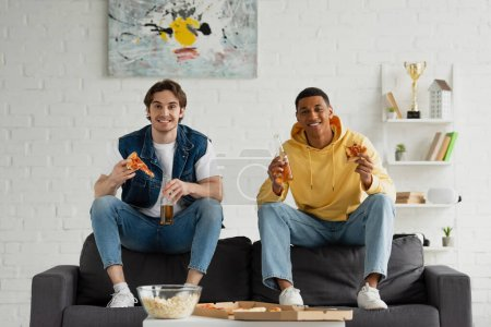 Photo for Happy interracial friends enjoying pizza slices, popcorn and beer on couch in modern living room - Royalty Free Image