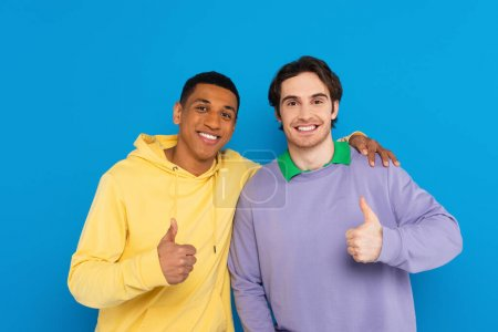 Photo for Smiling interracial friends showing thumbs up signs isolated on blue - Royalty Free Image
