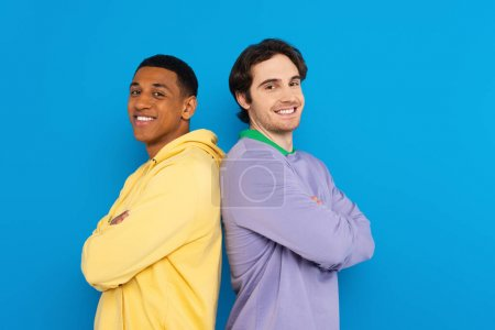 smiling interracial friends in back to back pose isolated on blue