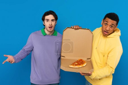 interracial hipsters holding box with pizza slice isolated on blue