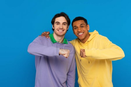 hugging interracial hipsters smiling with fist bump gesture isolated on blue