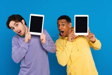 amis interracial avec des visages joyeux tenant des appareils numériques près des visages avec écran blanc isolé sur bleu