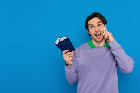 happy young man holding passports with air tickets in hands and speaking on cellphone isolated on blue