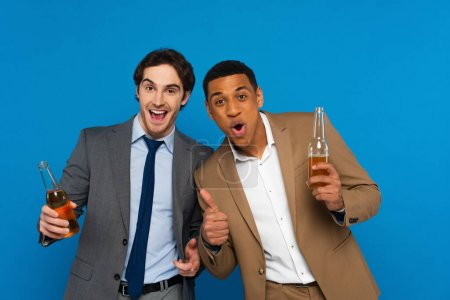 interracial friends in suits celebrating success with beer bottles and thumbs up gestures isolated on blue, banner
