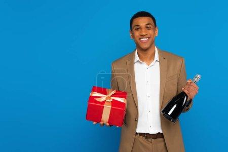 Lächelnder afrikanisch-amerikanischer Mann im eleganten Anzug mit Champagnerflasche und Geschenkbox isoliert auf blauem Grund