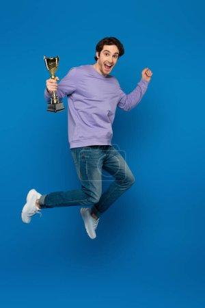 Photo pour Heureux homme souriant en sweat-shirt violet sauter avec coupe trophée sur fond bleu - image libre de droit