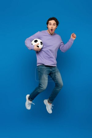 Photo pour Heureux homme souriant en sweat-shirt violet sautant avec le football sur fond bleu - image libre de droit