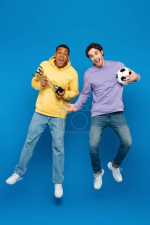 Photo pour Heureux homme afro-américain avec un ami léviter et tenant football et tasse sur fond bleu - image libre de droit